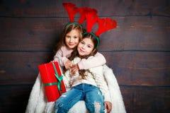 两个愉快一点微笑的女孩拥抱 圣诞节概念 鹿垫铁的微笑的滑稽的姐妹在演播室 免版税库存图片