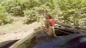 两个愉快微笑的年轻金发碧眼的女人挥动他们实施汽车的舱口盖在活动中反对森林 影视素材