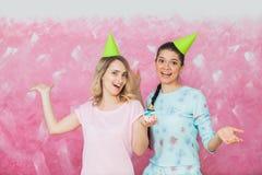 两个愉快的传神女孩庆祝生日聚会用杯形蛋糕 免版税库存图片