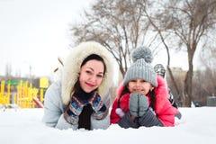 两个愉快的使用在操场a的女孩、母亲和女儿 免版税库存照片