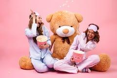 两个愉快的俏丽的女孩在获得的睡衣穿戴了乐趣 库存照片