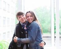 两个愉快的女学生在教室 免版税库存照片