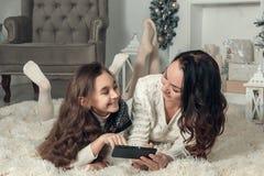 两个愉快的女孩、母亲和女儿在一个地板上说谎在新年 免版税图库摄影