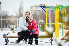 两个愉快的女孩、母亲和女儿坐在pl的一条长凳 图库摄影
