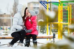 两个愉快的女孩、母亲和女儿坐在pl的一条长凳 免版税图库摄影