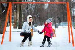 两个愉快的女孩、母亲和女儿坐在pl的摇摆 免版税库存照片