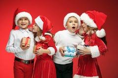 两个愉快的女孩和男孩在圣诞老人帽子有礼物盒的在演播室 免版税库存图片