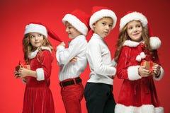 两个愉快的女孩和男孩在圣诞老人帽子有礼物盒的在演播室 库存照片
