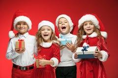两个愉快的女孩和男孩在圣诞老人帽子有礼物盒的在演播室 免版税图库摄影