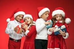 两个愉快的女孩和男孩在圣诞老人帽子有礼物盒的在演播室 库存图片