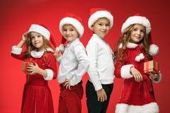 两个愉快的女孩和男孩在圣诞老人帽子有礼物盒的 库存照片