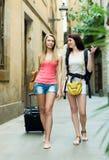 两个愉快的女孩在度假朝向对旅馆的 图库摄影