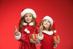 两个愉快的女孩在有礼物盒的圣诞老人帽子 免版税库存图片
