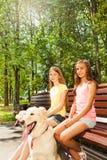 两个愉快的女孩坐长凳在公园 库存照片