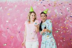 两个愉快的女孩庆祝与杯形蛋糕五彩纸屑a的生日聚会 免版税库存图片