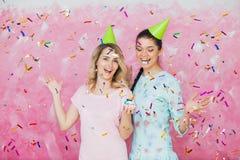 两个愉快的女孩庆祝与杯形蛋糕五彩纸屑a的生日聚会 库存照片