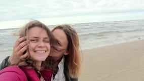 两个愉快的女孩沿冬天海滩走并且射击selfie 股票录像