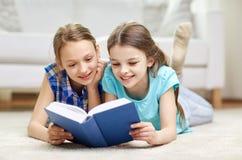 两个愉快的女孩阅读书在家 库存图片