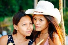 两个愉快的女性亚裔朋友画象海滩的 免版税图库摄影