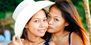 两个愉快的女性亚裔朋友画象海滩的 免版税库存照片