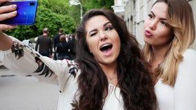 两个愉快的妇女朋友在街道上的电话做selfie 股票录像