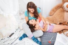 两个愉快的姐妹在和谈话在儿童居室 免版税库存照片