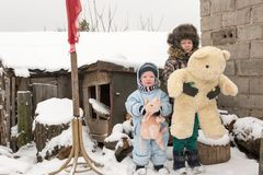 两个愉快的孩子在冬天塑造摆在与一头玩具猪和一头熊的衣裳在村庄房子的庭院里 第一雪, fam 免版税图库摄影