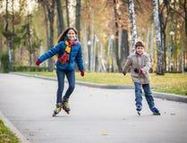 两个愉快的孩子在秋天公园乘坐在直排轮式溜冰鞋 免版税库存照片