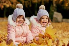 两个愉快的孩子在秋天在公园穿衣 图库摄影