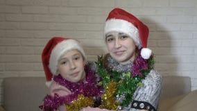 两个愉快的孩子女孩画象圣诞老人项目帽子的有在他们的肩膀的圣诞节闪亮金属片的,他们坐长沙发 影视素材