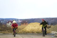两个愉快的孩子男孩和女孩骑马在寒冷骑自行车户外 库存图片