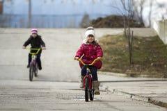 两个愉快的孩子男孩和女孩骑马在寒冷骑自行车户外 库存照片