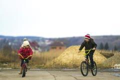 两个愉快的孩子男孩和女孩骑马在寒冷骑自行车户外 免版税库存照片