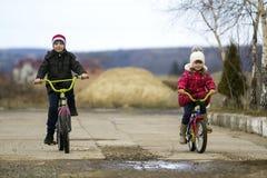 两个愉快的孩子男孩和女孩骑马在寒冷骑自行车户外 图库摄影