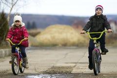 两个愉快的孩子男孩和女孩骑马在寒冷骑自行车户外 免版税库存图片