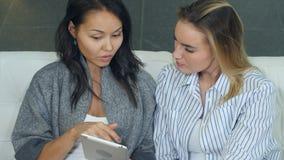 两个愉快的年轻女性朋友使用数字式片剂个人计算机,谈话和坐沙发 免版税库存照片