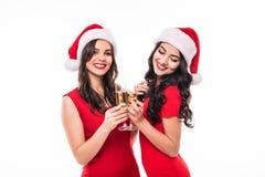 两个愉快的微笑的女孩画象拿着玻璃用香槟的红色礼服和圣诞老人帽子的,当敬酒和看凸轮时 免版税图库摄影