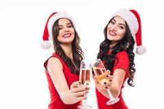 两个愉快的微笑的女孩画象拿着玻璃用香槟的红色礼服和圣诞老人帽子的,当敬酒和看凸轮时 库存图片