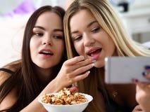 两个愉快的微笑的女朋友吃玉米花 免版税图库摄影