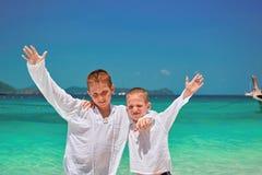 两个愉快的微笑的男孩在海滩的8-12岁拥抱并且上升他的手o 孩子在白色海角打扮 免版税库存图片