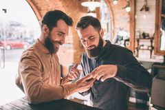 两个愉快的朋友在理发店 他们一起站立并且看电话 他们中的一个显示 免版税库存图片
