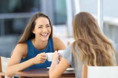 两个愉快的朋友谈话在餐馆大阳台 免版税库存图片