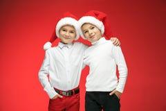 两个愉快的男孩在有礼物盒的圣诞老人帽子在演播室 免版税库存照片