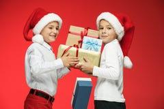 两个愉快的男孩在有礼物盒的圣诞老人帽子在演播室 库存照片