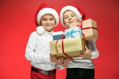两个愉快的男孩在有礼物盒的圣诞老人帽子在演播室 库存图片