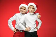 两个愉快的男孩在有礼物盒的圣诞老人帽子在演播室 图库摄影