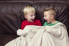 两个愉快的男孩坐一起看电视的长沙发 免版税库存照片