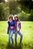 两个愉快的相当年轻姐妹 户外 免版税图库摄影
