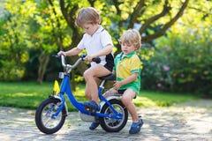 两个愉快的矮小的兄弟姐妹孩子获得乐趣一起在一辆自行车 免版税库存照片