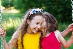 两个愉快的美丽的女孩坐跷跷板和谈话在summe 库存照片